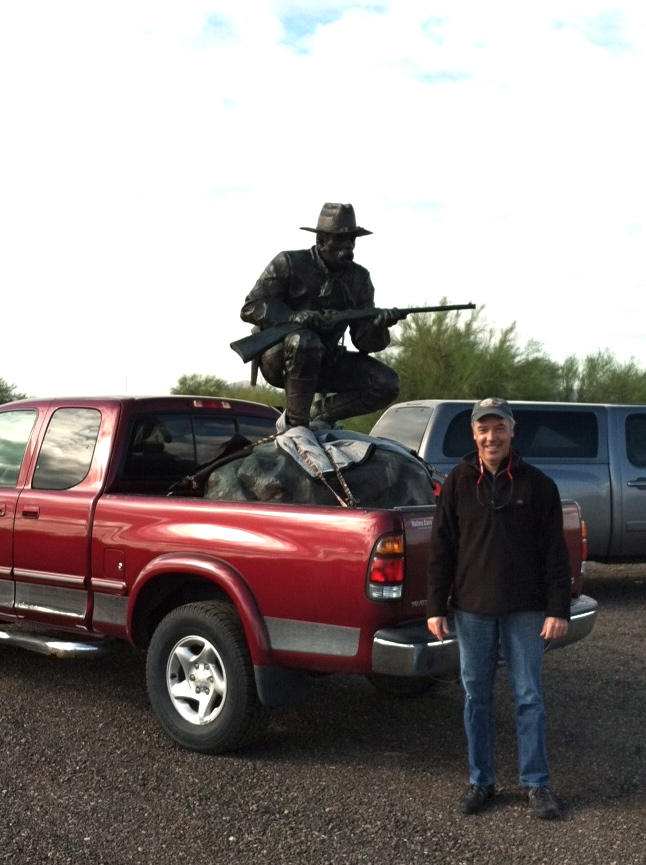 trooper sculpture in the back of a red truck with Sage Creek Gallery owner
