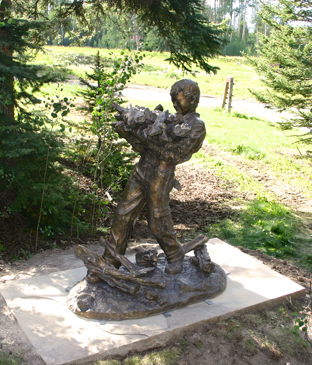 boy carrying wood bronze sculpture by scott rogers in telluride colorado